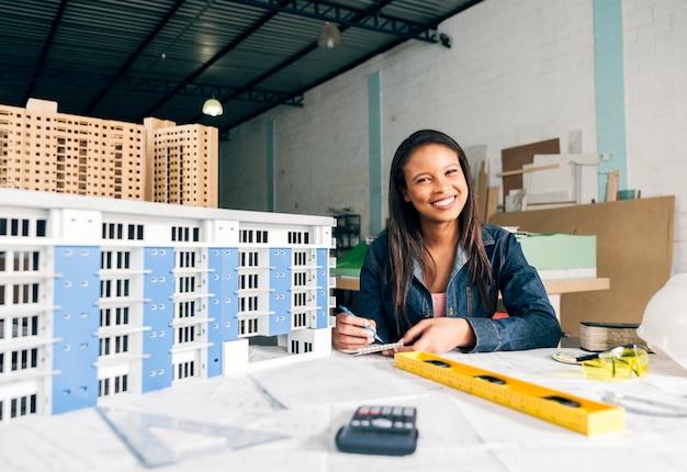 建物のモデルの近くのメモを取って笑顔のアフリカ系アメリカ人女性