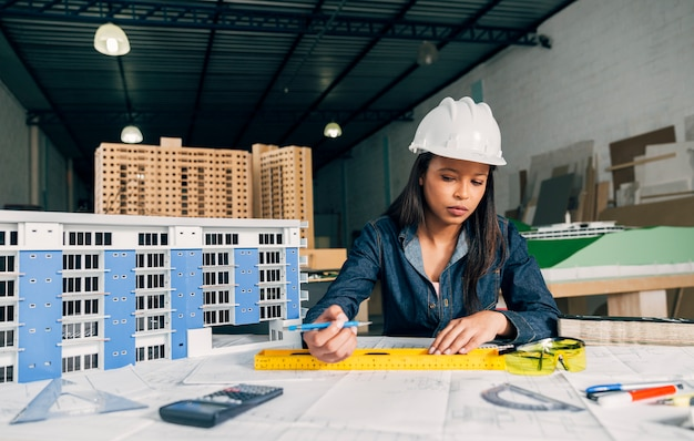 安全ヘルメットの建物のモデルの近くで働くアフリカ系アメリカ人女性
