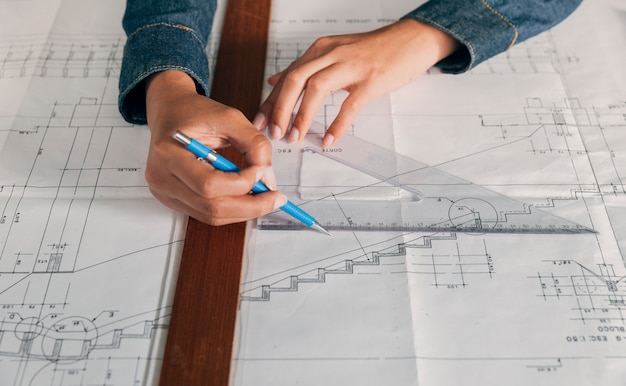 Женщина, работающая с геометрическим треугольником и ручкой
