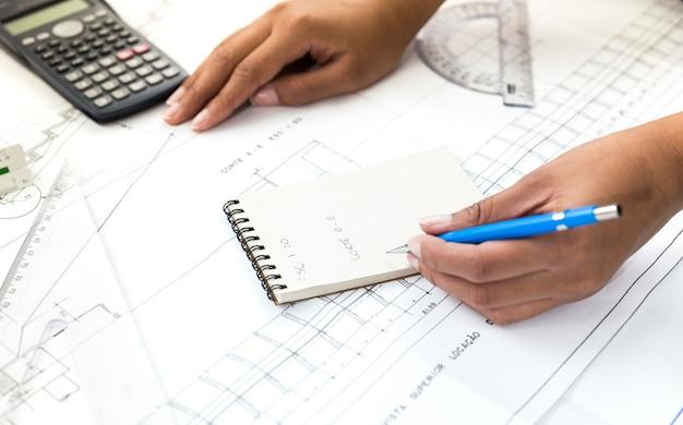 Женщина с ручкой заметок возле плана
