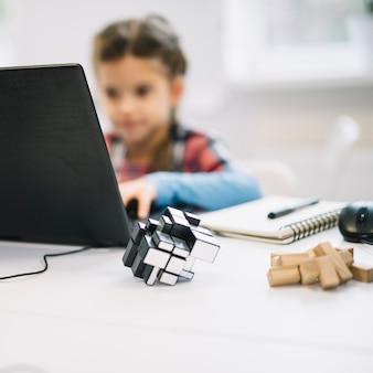 白い机の上のラップトップを使用して女の子の前でキューブパズル