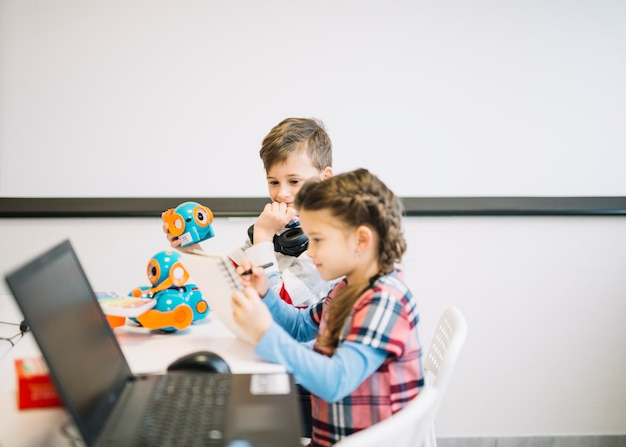 教室でペンでノートに描いている女の子を見て小さな男の子