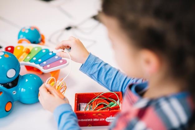 おもちゃに弦を修正する小さな女の子のクローズアップ