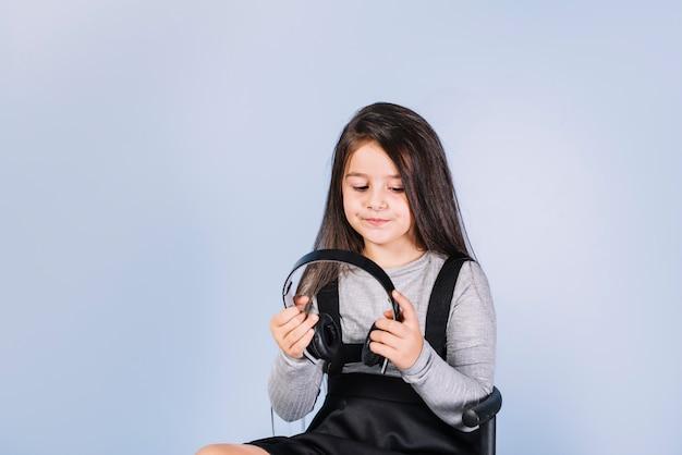 青い背景のヘッドフォンを見ている少女の肖像画