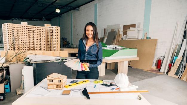 機器とテーブルの近くの色の例を持つアフリカ系アメリカ人女性の笑みを浮かべてください。