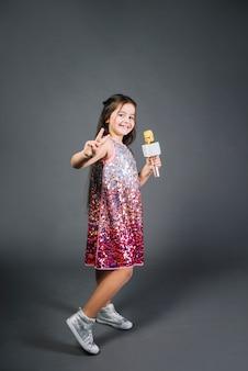 Девушка в платье с блестками держит микрофон, показывая знак победы на сером фоне