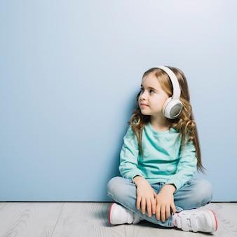 堅木張りの床に座ってブロンドの女の子がよそ見ヘッドフォンで音楽を聴く