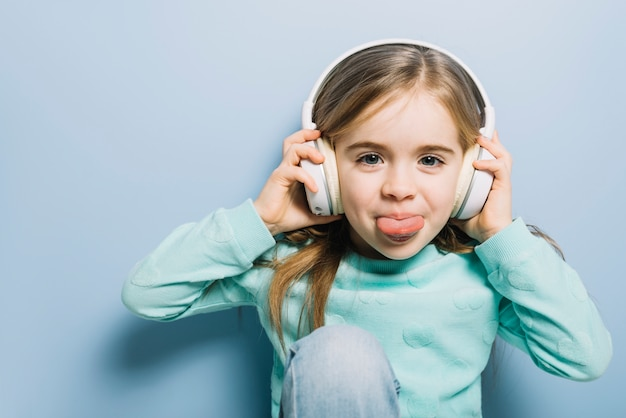 かわいい女の子が彼女の舌を突き出てヘッドフォンで音楽を聴く