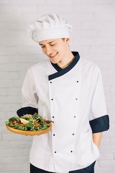 Кук держит деревянную тарелку с салатом