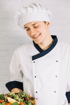 Молодой повар держит деревянную тарелку с салатом