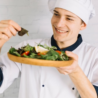 Мужской повар смотрит на деревянную тарелку с салатом