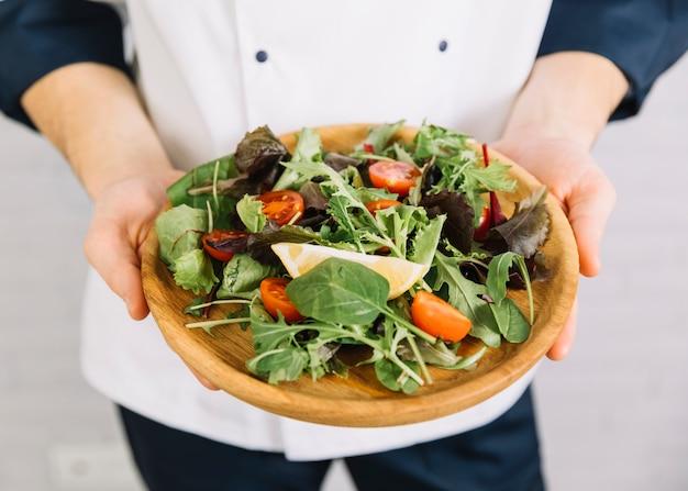 Повар держит большую деревянную тарелку с салатом