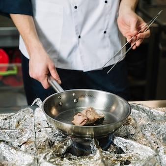 ストーブの上のフライパンで白いフライパンで調理します。