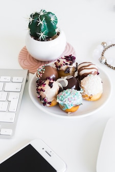 Клавиатура возле смартфона, браслеты, комнатное растение и печенье на тарелке