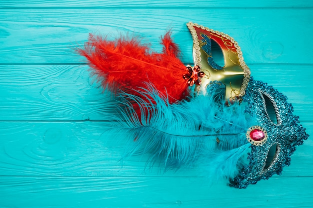 Две красные и синие венецианские карнавальные маски на синем деревянном столе