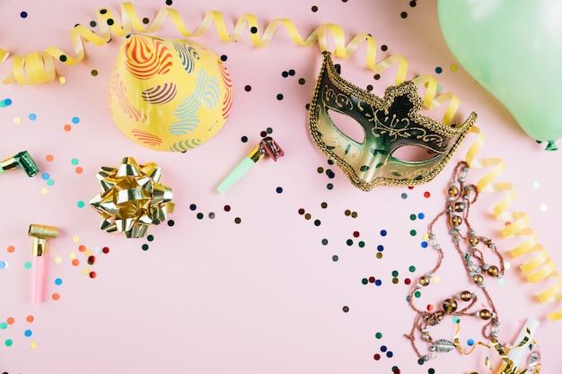ピンクの背景にパーティーの装飾が施されたゴールデン仮装カーニバルマスク