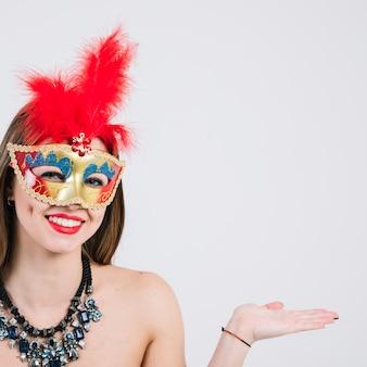 仮面舞踏会のカーニバルマスクと白い背景で身振りで示すネックレスを着ている女性