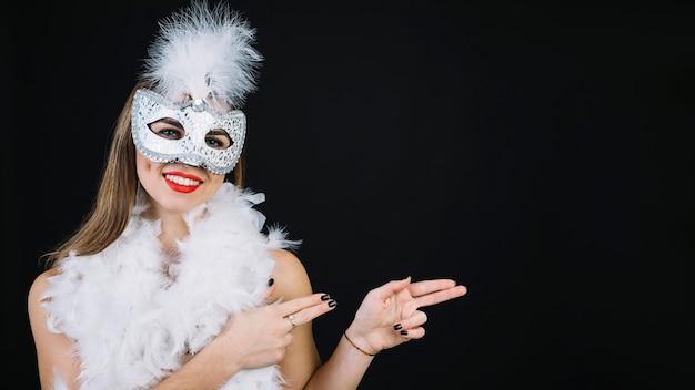 白い背景で身振りで示すカーニバルマスクを着て笑顔の女性の肖像画