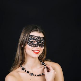 仮面舞踏会のカーニバルマスクを身に着けているビーズのネックレスを持つ女性の笑みを浮かべてください。