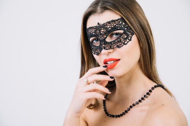 仮面舞踏会のカーニバルマスクとビーズのネックレスを着てトップレスの女性