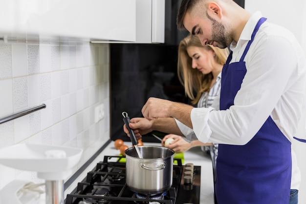 若い男が女性の近くの鍋に水を塩漬け