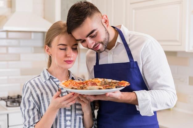 皿の上のピザの臭いがするカップル