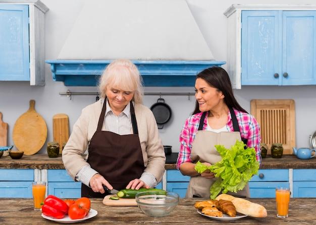 台所で野菜を準備するための彼女の母を助ける娘