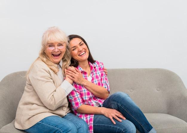 母と娘が一緒に笑ってソファーに座っていたの幸せな肖像画
