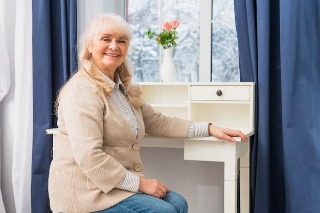 机の近くの窓の前に座っている笑顔の年配の女性の肖像画