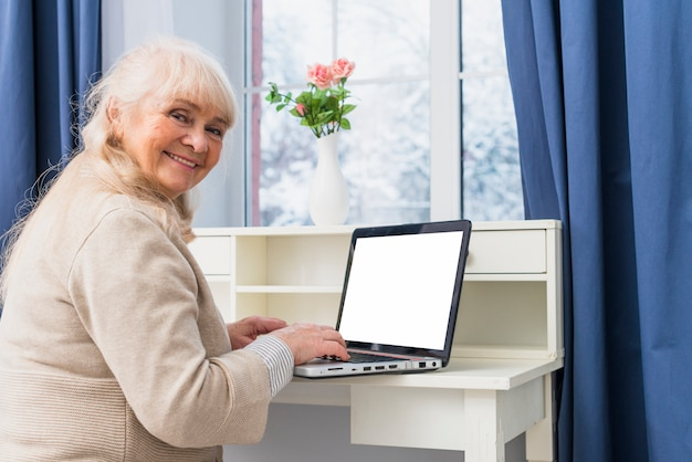 空白の白い画面を持つラップトップを使用して笑顔の年配の女性の肖像画