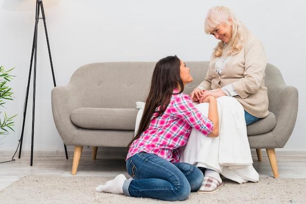 娘が自宅のソファの上の彼女の年配の母親の近くのカーペットの上に座って