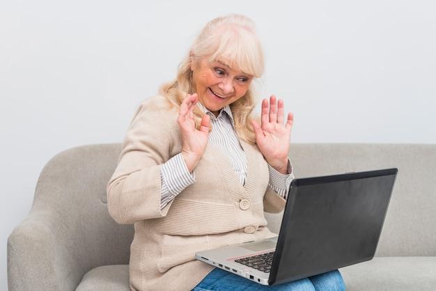 手を振っているラップトップでビデオチャットを持つ幸せな年配の女性