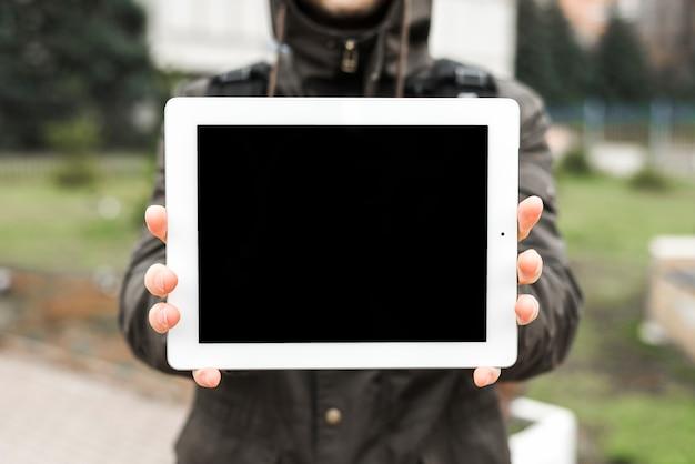 デジタルタブレットの空白の画面を示す人の手のクローズアップ