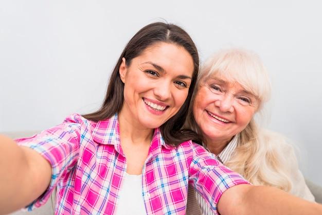 白い背景に対してセルフポートレートを取る彼女の娘と一緒に陽気な年配の女性