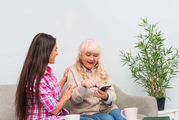 携帯電話を使用して彼女の年配の母親を支える若い女性