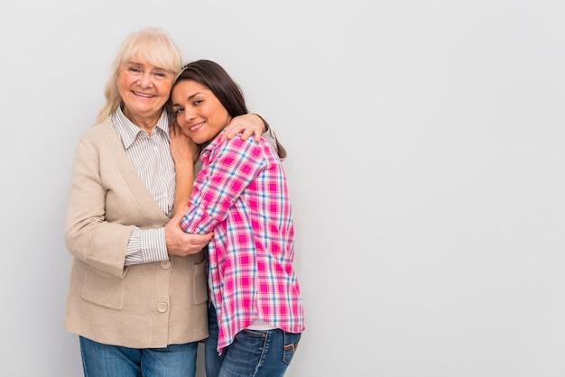 白い壁に立っている彼女の若い娘を抱きしめる年配の女性