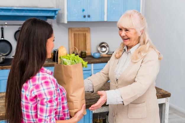 若い女性が台所で彼女の年配の母親に食料品の袋を与える