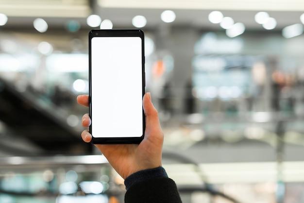 モールでスマートフォンの白い空白の表示を示す手のクローズアップ