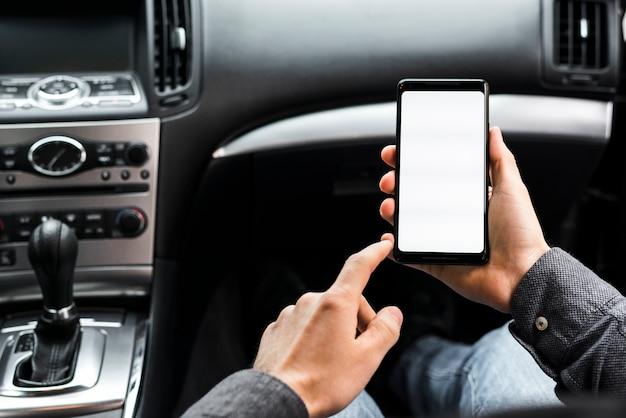 車の中で座っている白い表示画面を持つスマートフォンを使用して手のクローズアップ