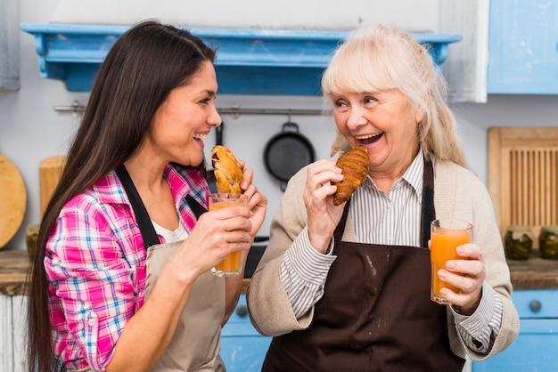 若い娘と年配の女性がジュースのガラスを保持している焼きたてのクロワッサンを食べる