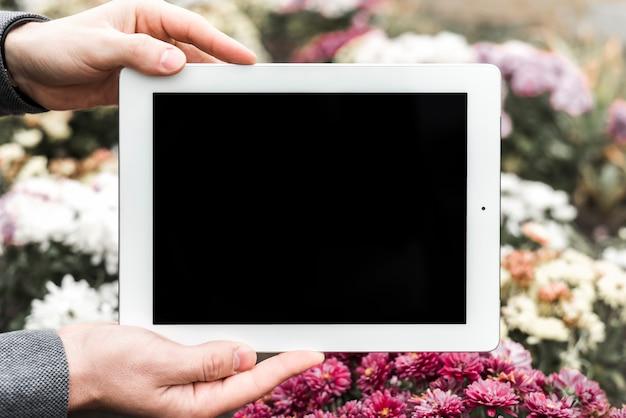 花の前にデジタルタブレットを持っている手のクローズアップ