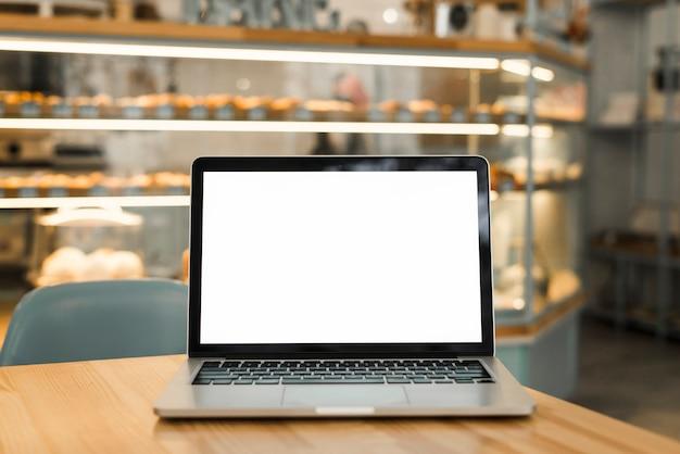 コーヒーショップのテーブルの上の空白の白い画面表示と開いているノートパソコン