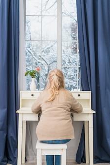 Вид сзади старшей матери, сидящей за столом возле закрытого окна