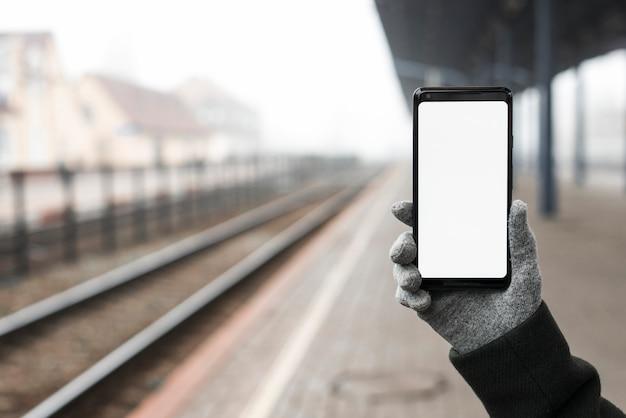 鉄道駅で空白の白い画面を示す携帯電話を保持している手袋を身に着けている手のクローズアップ