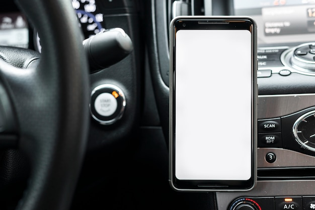 Смартфон с белым экраном на приборной панели автомобиля