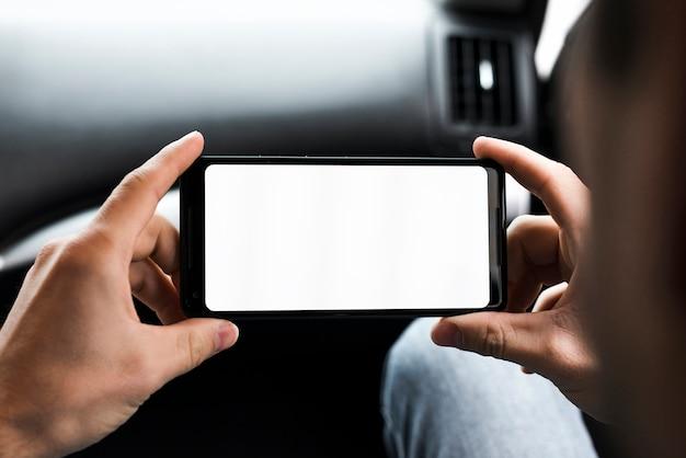 彼の携帯電話の白い画面表示を見ている男の手のクローズアップ