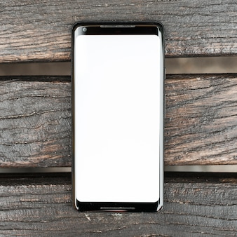 木製の織り目加工の板に白い画面表示を持つ携帯電話