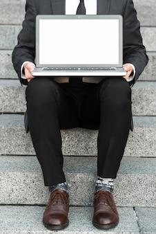 Крупный план бизнесмена, сидящего на лестнице с открытым ноутбуком на коленях