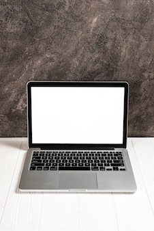 Ноутбук с пустой белый экран на белом деревянном столе против бетона