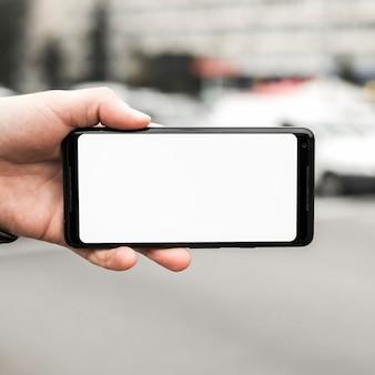 空白の白い画面を示す携帯電話を持つ手のクローズアップ
